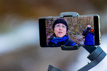Gimbal Mobile Phone Tripod Head Stabilizer, On Its Screen A Mature Woman Filming A Video And A Photographer Taking A Photo Behind, Blurred Background, Dutch Nature Reserve With Trees On A Hill