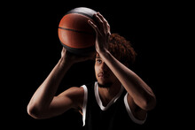 Professional Basketball Player Holding A Ball Against Black Background. Serious Concentrated African American Man In Sports Uniform