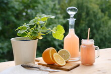 Fresh Fruit Smoothies In A Decanter And A Mug On A Background Of Green Garden Foliage, Orange Sliced into Slices, Concept Of Summer Refreshing Fresh Citrus Drinks, Vegetarian Food