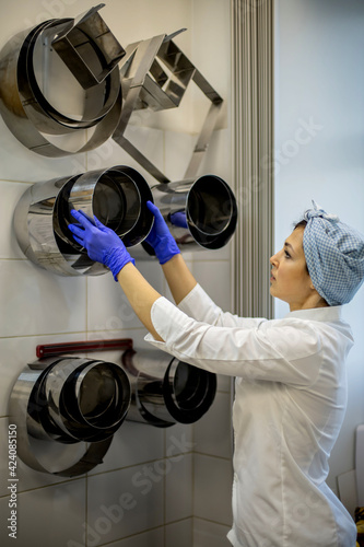 Papel de parede Cheerful woman chef in white uniform looking on metal bakeware meal mold dishes