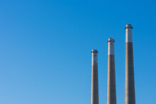 Three Towering Concrete Smokestacks Of Decommissioned Power Plant Soaring Into Blue Sky.
