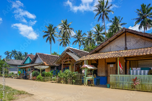 Fotomural Traditional house of beachside village with coconut trees under blue skies