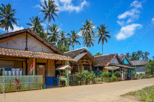 Fotografía Traditional house of beachside village with coconut trees under blue skies