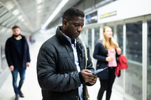 Portrait Of African American Male Passenger Waiting For Train On Subway Platform And Reading Timetable In Phone