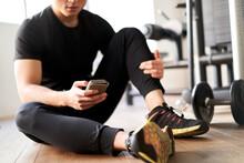 トレーニング中の足の痛みについて対処法を調べるアジア人男性