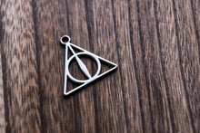 Silver Necklace Of Deathly Hallows On Wood Background. Symbol Of Harry Potter Fans.