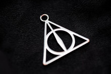 Deathly Hallows On Black Background Of Fabric Texture.