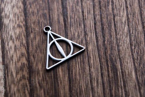 Foto Silver necklace of deathly hallows on wood background