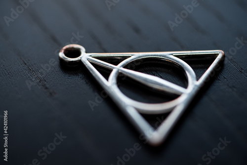 Fotografia Close up silver necklace focus deathly hallows.