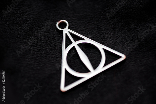 Foto Deathly hallows on black background of fabric texture.