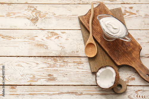 Gravy boat with coconut cream on light wooden background