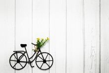 Bicycle With Flowers On Wooden Background