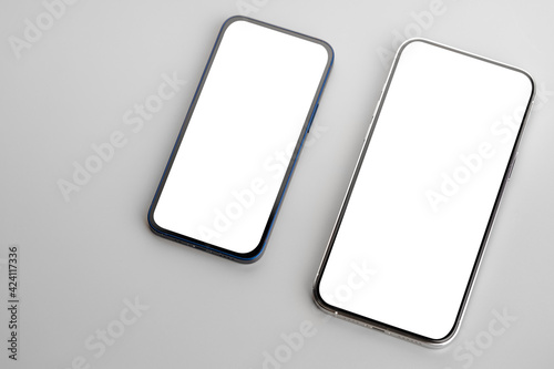 Fototapeta Two smartphones with blank white screen on gray background obraz