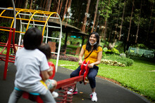 Mother Playing See Saw With Her Kids In The Playground