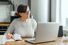 Focused Retired Woman Is Learning Online, Using A Laptop For Watching Online Classes, Webinar, Senior Female Takes A Notes Sitting In The Kitchen At Home
