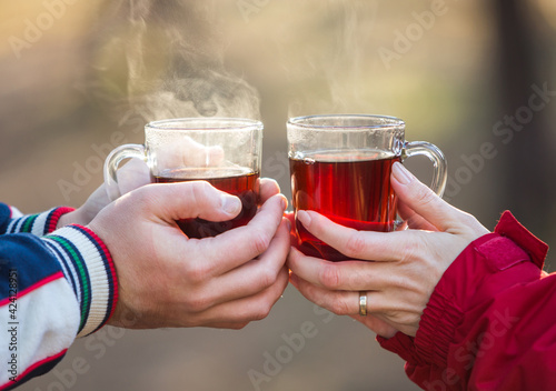 Loving young couple holding hands and hot tea outdoors