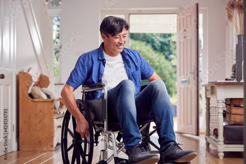 Mature Asian Man In Wheelchair Pushing Himself Along Hallway At Home Fototapet