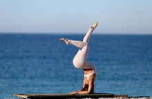 Beautiful Woman In White Jumpsuit Is Engaged In Yoga On The Background Of The Sea.