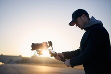 Young Man Filming With Camera And Gimbal. Videographer Standing Against City At Sunrise. Prague, Czech Republic