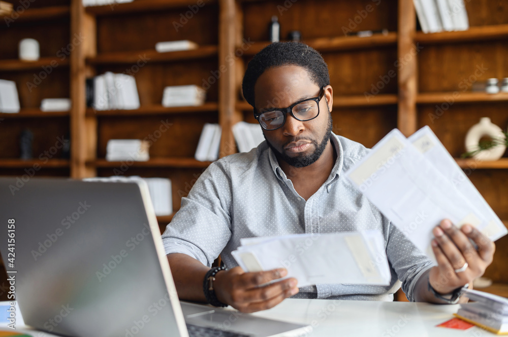 Fototapeta Serious black man with black square glasses, concentrated reading from whom letters, received a bad news, male manager employee unpacking banking notification, law order or paper document at workplace