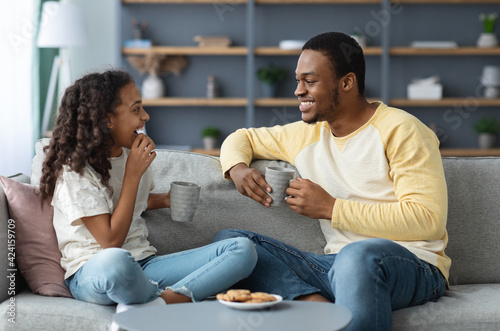 Cute black father and daughter drinking tea with cookies