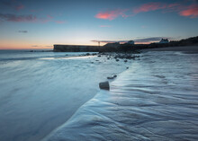 Sunrise On Seaton Sluice Beach And Harbour Mouth In The Coast Of Northumberland, England, UK.