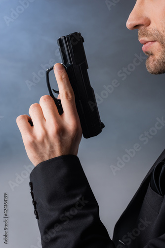 Obraz cropped view of businessman holding gun on grey background with smoke - fototapety do salonu