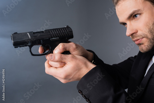 Obraz young businessman aiming with gun on grey background with smoke - fototapety do salonu