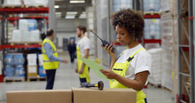 African Female Warehouse Manager Holding Clipboard And Using Walkie-talkie While Checking Inventory.