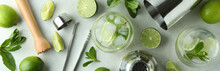 Glass Of Mojito Cocktail And Ingredients On White Textured Table