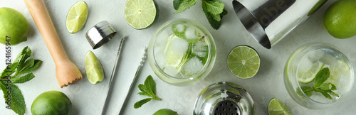 Fototapeta Glass of mojito cocktail and ingredients on white textured table obraz