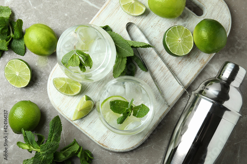 Obraz Board with glasses of mojito cocktail and ingredients on gray textured table - fototapety do salonu