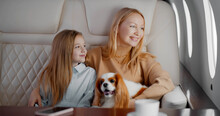 Mature Mother And Preteen Daughter Travelling On Personal Jet With Dog
