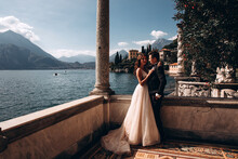 Walk For The Newlyweds Along The Embankment On The Shores Of The Italian Lake. The Pier Is Made Of Stone. Summer Sunny Day.