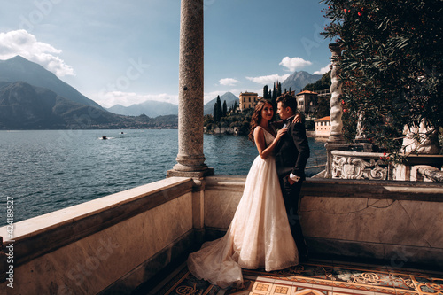 Walk for the newlyweds along the embankment on the shores of the Italian lake Wallpaper Mural