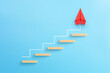 Leinwandbild Motiv Wooden block stacking as step stair with red paper plane on blue background, Ladder of success in business growth concept, copy space