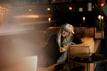 Mature Woman In Cafe Using Cell Phone