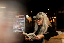 Mature Woman In Cafe Reading Book