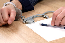 A Detainee At The Police Station. One Hand Is Cuffed, The Other Is Unbuttoned, And There Is A Pen In His Hand For Writing Explanations. Arrest, Bail, Felony, Jail. The Criminal's Fingerprints