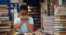 Stressed Afro-american Teen Student Crying Sitting At Table With Stack Of Books In Library