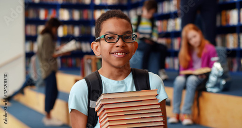 Fotografie, Obraz Middle eastern boy holding stack of books against multi colored bookshelf in library