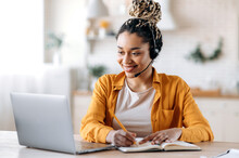 Concentrated Confident Friendly African American Girl In Headset, Call Center Operator, Manager, Agent Of Support Service, Conducts Online Consultation, Video Briefing, Taking Notes, Smiling Friendly