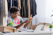 African American Owner Of Showroom Holding Wooden Mannequin Near Devices And Packages On Table