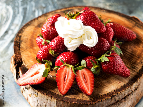 Fototapeta eine baumscheibe mit frischen süßen erdbeeren und einem klecks sahne obraz