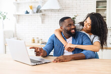 Happy African-American Couple With A Laptop Planning Vacation Together, Using Computer App For Booking Hotels Or Tour, Smiling Man Points Finger On The Screen, A Woman Hugs Him And Laughs