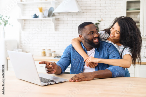 Canvas Print Happy African-American couple with a laptop planning vacation together, using co