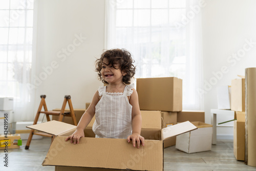 Fototapeta Cheerful cute toddler little baby girl playing inside cardboard box while family