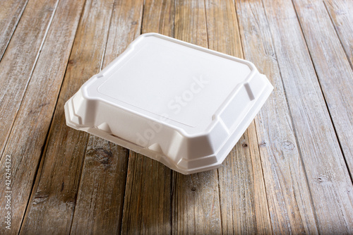 Fototapeta A view of a food styrofoam container on a table.