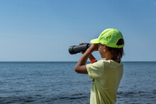 White Caucasian Boy With Black Spyglass Stand On Seashore And Look Ahead, To The Horizon,  Copyspace.Active Lifestype, Dreaming About Sea Adventures.