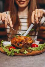 Attractive Woman With A Fork And A Knife Cuts A Large Portion Of Fried Meat At A Table In A Restaurant